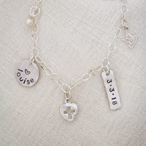 Personalized confirmation charm bracelet with cross, dove, and pearl.