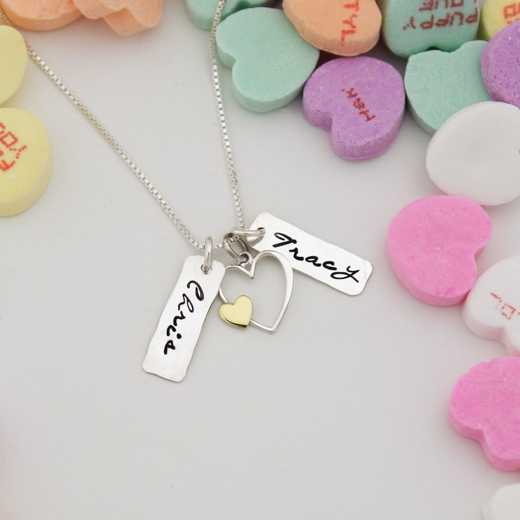Silver and gold heart necklace with name tags for husband and wife.