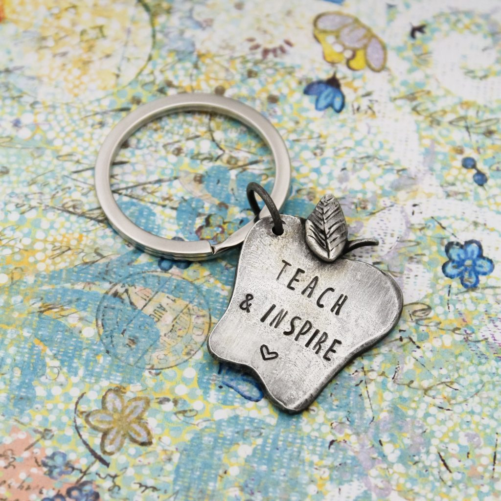 Hand stamped teach & inspire keychain in pewter.