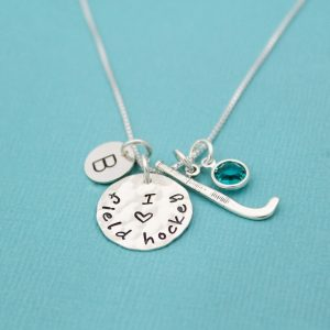Hand stamped i heart field hockey necklace with field hockey stick charm, birthstone, and initial.