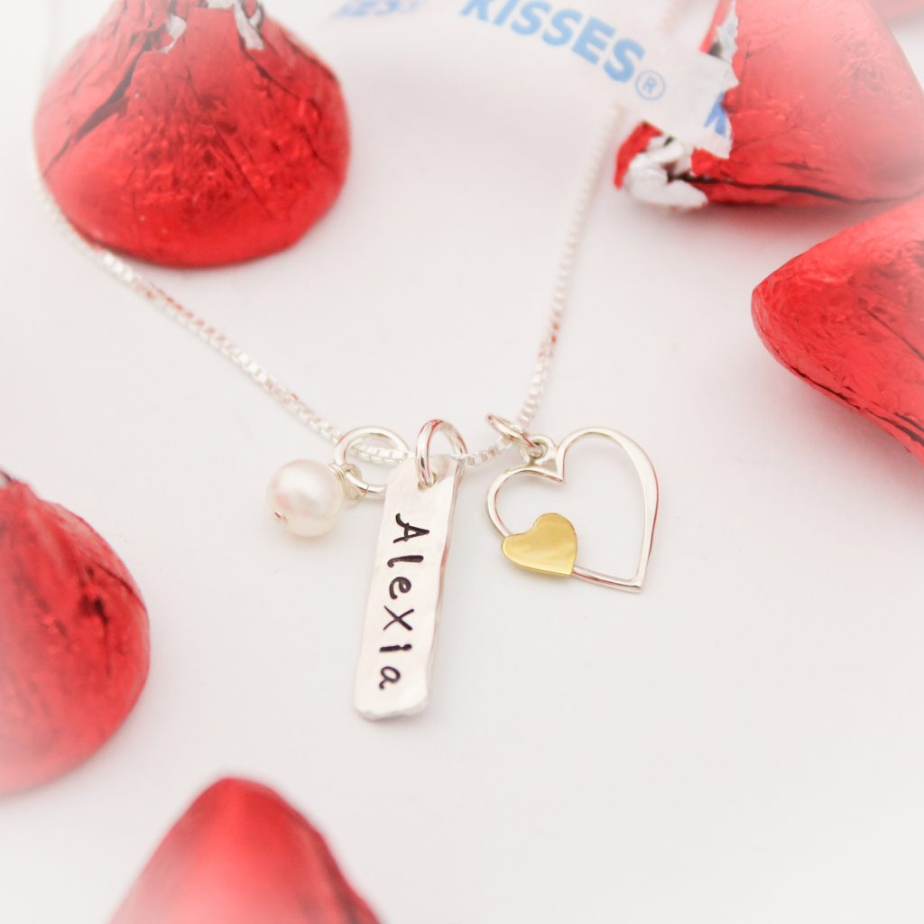 Silver and bronze heart with personalized tag name and pearl.